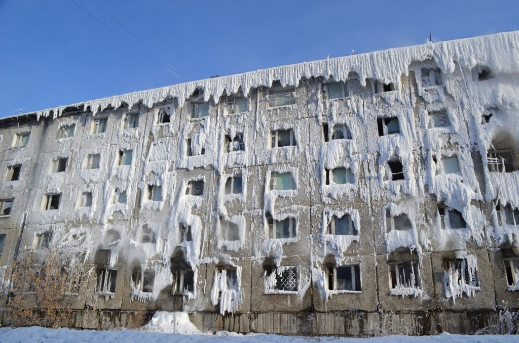 The facade of a five story building covered is snow and ice.