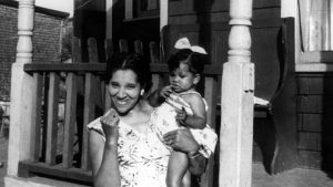 A black and white photo of a woman holding her child in one arm, smiling, standing in front of her front porch