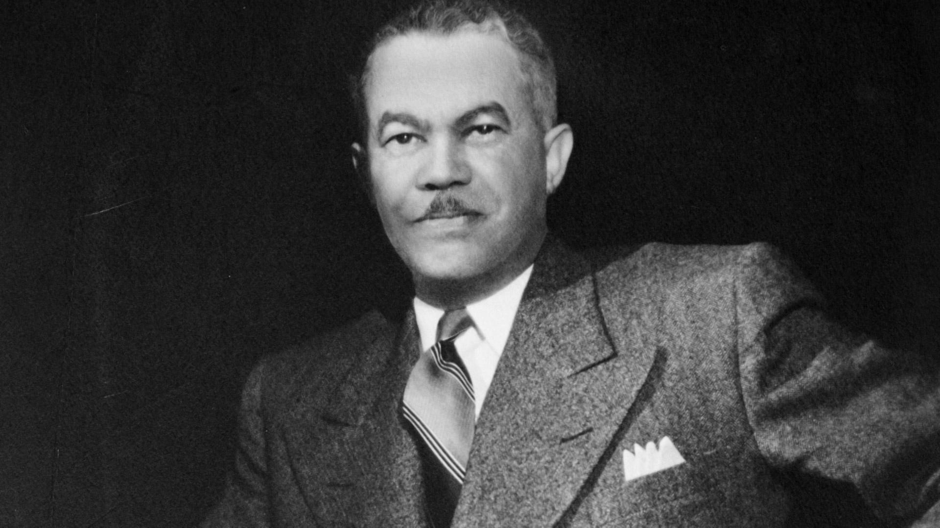 Black and white portrait of a man wearing a suit, looking into the camera with a neutral expression