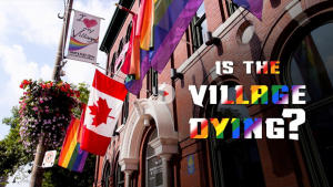 Rainbow flags and a Canadian flag hanging from a brick building.
